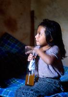 A young girl hits a soda bottle, Santiago Atitlan, Guatemala