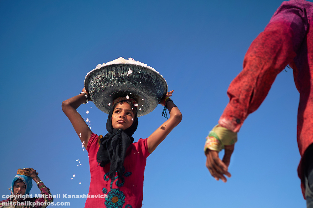 From salt workers in salt pans around Dwarka, Gujarat, India. Girl salt worker with a tub loaded with salt over her head.