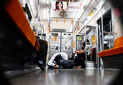 A man who has removed his shoes sleeps cross-legged on the floor of a train in Tokyo, Japan. The Japanese are well known for their civility and politeness,  but a recent governmental campaign to clamp down on lewd behavior that may inconvenience others -- including talking on cell phones and applying makeup while commuting on a train -- was fueled by a decline in etiquette and manners.