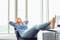 Full-length of businesswoman relaxing with feet up at desk in creative office