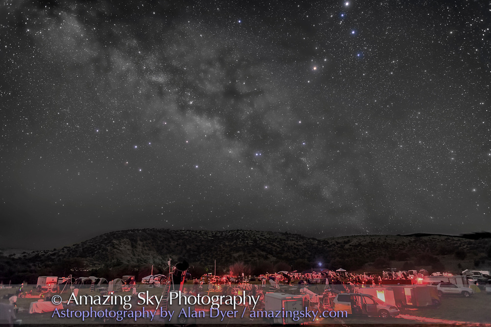 The galactic centre region of the Milky Way in Sagittarius and Scorpius, over the upper field of the Texas Star Party, near Fort Davis, Texas, May 13, 2015. About 600 people gather here each spring for a star party under very dark skies near the MacDonald Observatory. Sagittarius is left of centre and Scorpius is right of centre with the planet Saturn the bright object at the top edge right of centre. The dark lanes of the Dark Horse and Pipe Nebula areas lead from the Milky Way to the stars of Scorpius, including Antares. The semi-circular Corona Australis is just clearing the hilltop at left of centre.<br /> <br /> This is a composite of 5 x 3 minute exposures with the camera tracking the sky for more detail in the Milky Way without trailing. Each tracked exposure was at ISO 1600. The ground comes from 3 x 1.5-minute exposures at ISO 3200 taken immediately after the tracked exposures but with the drive turned off on the tracker. All are with the 24mm lens at f/2.8 and filter-modified Canon 5D MkII camera. The ground and sky layers were stacked and layered in Photoshop. The tracker was the Sky-Watcher Star Adventurer. High haze added the natural glows around the stars &mdash; no filter was employed here. This version of the image has been processed to make the view better resemble what you see with the unaided eye, in a largely monochrome and softer view than the colourful and high-contrast views commonly presented in astrophotos. Even at that there is more fine structure present in the Milky Way than the unaided eye usually sees, though binoculars beging to reveal that smaller detail. I have left some colours in some stars and in the foreground of landscape scenes.