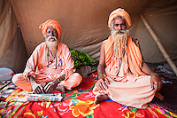 Two naga baba men sit in a tent during the kumbh mela festival
