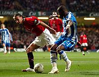 Photo: Ed Godden.<br />Manchester United v Wigan Athletic. The Carling Cup Final. 26/02/2006. Rio Ferdinand (L) keeps Wigans Henri Camara (R) off the ball.