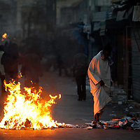 A merchant walks up a street with burning barricades during riots in Dakar, Senegal, 21 February 2012. Violent demonstrations against incumbent President Abdoulaye Wade's re-election bid continue in the capital Dakar ahead of presidential elections. Protesters are demonstrating against a ruling by the country's top judges allowing President Abdoulaye Wade to seek a third term in office. Presidential elections are scheduled for 26 February 2012. © Sylvain Cherkaoui