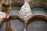 View from above showing a young boy's legs reflected in the dying pits; beside him a pile of skins resembles a mummy, Chouara Tannery, Fez, Morocco, pictured on February 25, 2009 in the evening. The Chouara tannery is the largest of the four ancient tanneries in the Medina of Fez where the traditional work of the tanners has remained unchanged since the 14th century. It is composed of numerous dried-earth pits where raw skins are treated, pounded, scraped and dyed. Tanners work in vats filled with various coloured liquid dyes derived from plant sources. Colours change every two weeks, poppy flower for red, mint for green, indigo for blue, chedar tree for brown and saffron for yellow. Fez, Morocco's second largest city, and one of the four imperial cities, was founded in 789 by Idris I on the banks of the River Fez. The oldest university in the world is here and the city is still the Moroccan cultural and spiritual centre. Fez has three sectors: the oldest part, the walled city of Fes-el-Bali, houses Morocco's largest medina and is a UNESCO World Heritage Site;  Fes-el-Jedid was founded in 1244 as a new capital by the Merenid dynasty, and contains the Mellah, or Jewish quarter; Ville Nouvelle was built by the French who took over most of Morocco in 1912 and transferred the capital to Rabat. Picture by Manuel Cohen.