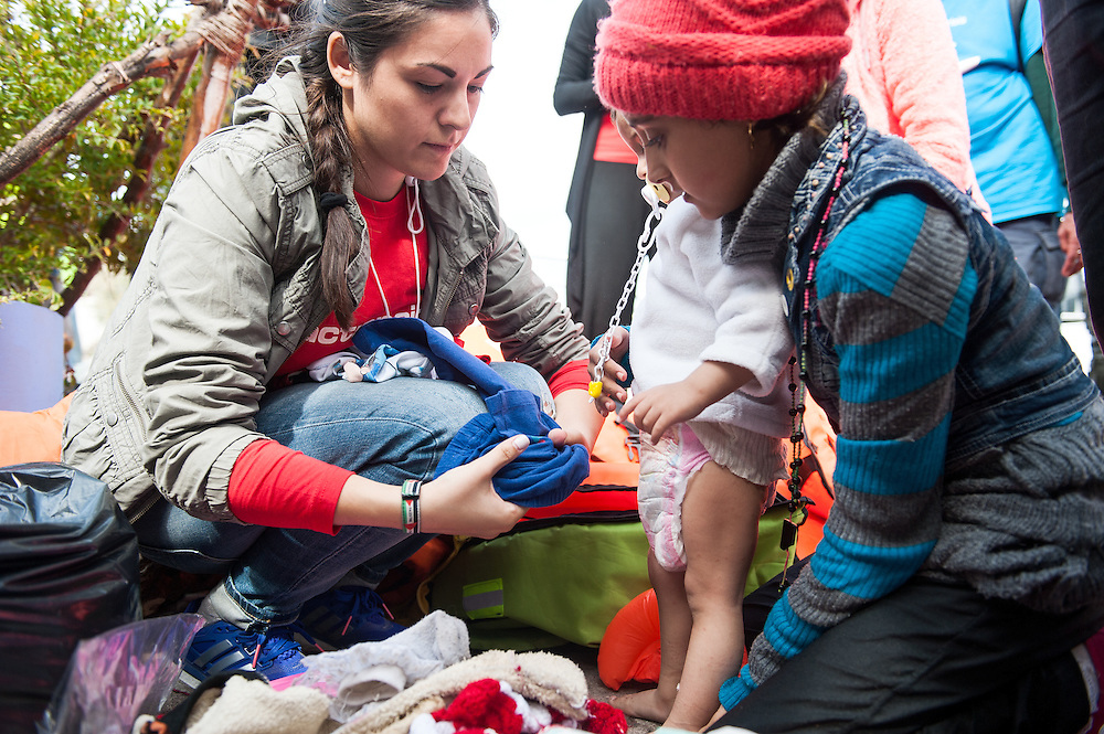 Constantina Strikou, programme coordinator of ActionAid Hellas, helps Syrian girls to change their wet clothes at  the fishing harbour of Skala Sykamias, Lesvos, Greece.