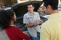Couple talking to mechanic by open car hood