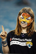 A Jacksonville Jaguars fan with a painted face shows who she thinks is number one during the NFL week 14 football game against the Houston Texans on Thursday, Dec. 5, 2013 in Jacksonville, Fla. The Jaguars won the game 27-20. ©Paul Anthony Spinelli