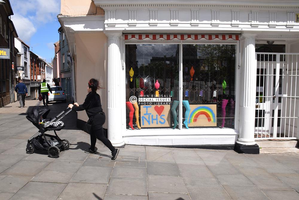 I love NHS & rainbow poster in shoe shop window during Coronavirus lockdown, Norwich UK May 2020