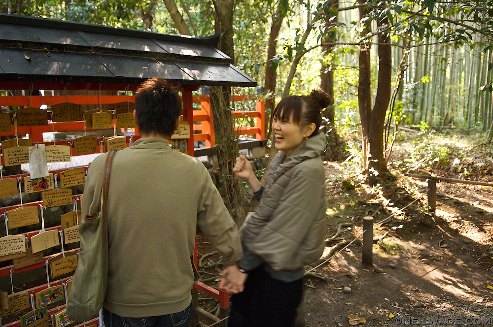 A Japanese university student reacts to a funny prayer she read on a piece of wood at a Shinto shrine in Kyoto, Japan.