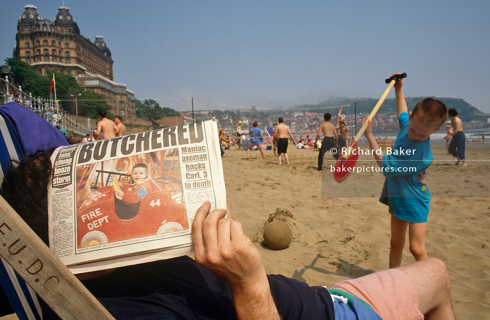 """Using a tabloid newspaper, a father seeks shelter from sunshine while sitting in a council deck chair. On the front page of the paper is a headline saying """"Butchered' showing a picture of an unfortunate young 3 year-old boy murdered by a maniac axeman. Close-by is the man's own son who is digging a hole furiously in the sand. He looks uncannily like a slightly older version of the murdered boy. This coincidence is heightened because of the body-language of the digging lad, seemingly about to chop an unseen object with his red spade. Both man and boy are on holiday at the northern English seaside resort of Scarborough, North Yorkshire and they are otherwise having a great time on South Beach, near the Grand Hotel building, high up on the cliff."""