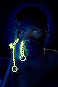 Portrait of a young man with glowing yellow chain.Black light