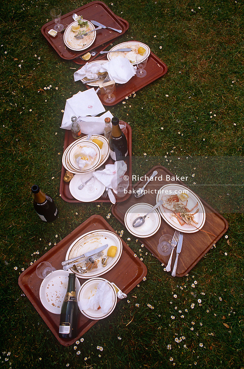 Discarded leftovers of picnic food and drink on the grass during the annual Chelsea Flower Show, the annual event held by the Royal Horticultural Society (RHS) in London. Plates of shellfish and puddings plus bottles and corks from champagne and Bucks Fizz, for example, are seen on the catering tays on a patch of grass near show pavilions.