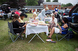 © Licensed to London News Pictures. 19/06/2014. Ascot, UK. People picnic amongst cars in the car park.  Day three, Ladies Day, at Royal Ascot 19th June 2014. Royal Ascot has established itself as a national institution and the centrepiece of the British social calendar as well as being a stage for the best racehorses in the world. Photo credit : Stephen Simpson/LNP