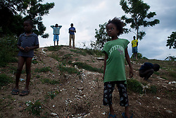 A group of children stand on a hill next to an area that suffered a mudslide that killed a family during the storm. Hurricane Sandy brought heavy flooding to the region , destroyed crops and livestock and will seriously hinder farmers' abilities to grow food in the future.