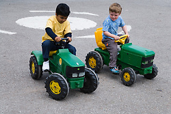 Young boys riding on toy tractors,