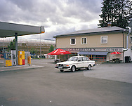 A Volvo 240 is parked outside a fast food restaurant