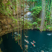 People swimming in cenote Ikil. Yucatan, Mexico.