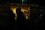 A man is seen sleeping in his shop at the Calais camp, France. FEDERICO SCOPPA/CAPTA