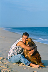 dog being hugged by a man on the beach in East Hampton, NY