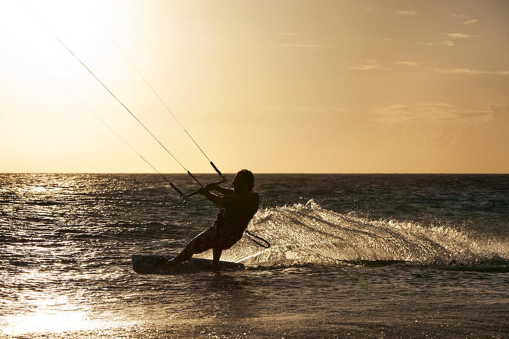 Dutch Antilles, Bonaire, Silhouette of Kitesurfer riding along waves at sunset on Caribbean Sea