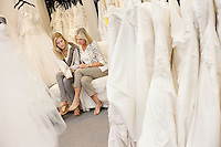 Mother and daughter looking at footwear in bridal store
