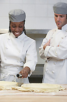 Male chef watching female chef preparing food in kitchen