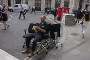 A workman peels a banana before removing old office chair furniture in a street on 13th September 2016, in the City of London, England.
