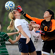Kris Wilson/News Tribune<br /> Helias midfielder Kaysie Scheuler takes a shot to the nose as Springfield Catholic goalkeeper Mary Wichmer punches the ball away from the goal area as the two teams square off in the Capital City Invitational at 179 Soccer Park.