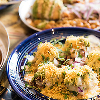 Dishes at Chai Pani: Bhel Puri (puffed rice dish on blue plate), Samosa Chat (two samosas on spicy garbanzo bean stew on metal plate). Chai Pani is an Indian Street Food restaurant located at 22 Battery Park Avenue in Downtown Asheville, North Carolina.