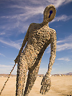 Art installation with lock and key theme shaped like a man, 'walks' in the desert at Burning Man Festival.