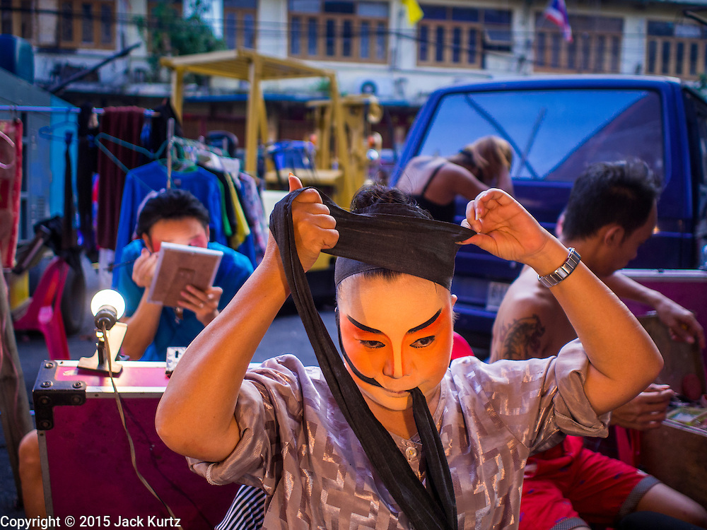 16 JANUARY 2015 - BANGKOK, THAILAND:  A performer with Sai Yong Hong Opera Troupe gets into character before performing at the Chaomae Thapthim Shrine, a Chinese shrine in a working class neighborhood of Bangkok near the Chulalongkorn University campus. The troupe's nine night performance at the shrine is an annual tradition and is the start of the Lunar New Year celebrations in the neighborhood. Lunar New Year, also called Chinese New Year, is officially February 19 this year. Teochew opera is a form of Chinese opera that is popular in Thailand and Malaysia.   PHOTO BY JACK KURTZ