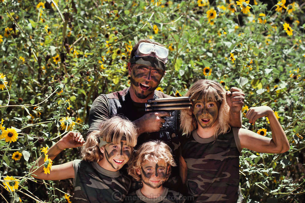 A camouflaged family of paintball combatants at Sat Cong Village war games/paintball combat park near Los Angeles, California, USA. The father of the three girls holds his gun to his oldest daughter's head.