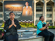 20 JANUARY 2017 - BANGKOK, THAILAND: Women pray in front of portrait honoring the late King on the plaza in front of Bangkok's City Hall. Hundreds of municipal workers and civil servants made merit by praying and presenting alms to 89 Buddhist monks Friday to mark 100 days of mourning since the death of revered Bhumibol Adulyadej, the Late King of Thailand. The significance of 89 monks is that the King, who died on October 13, 2016, was a few weeks short of his 89th birthday.        PHOTO BY JACK KURTZ