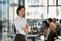 Businesswoman standing in office with group of office workers in background.