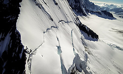 Cracks in the snow on the mountainside above the Fairweather Glacier appear like they could cause an avalanche in Glacier Bay National Park and Preserve.<br /> <br /> Glacier Bay National Park is located in southeast Alaska. Known for its spectacular tidewater glaciers, icefields, and tall costal mountains, the park is also an important marine wilderness area. The park a popular destination for cruise ships, is also known for its sea kayaking and wildlife viewing opportunities. <br /> <br /> Glacier Bay National Park is home to humpback whales which feed in the park's protected waters during the summer, both black and grizzly bears, moose, wolves, sea otters, harbor seals, steller's sea lions and numerous species of sea birds. <br /> <br /> The dynamically changing park, known for its large, contiguous, intact ecosystems, is a United Nations biosphere reserve and a UNESCO World Heritage site.