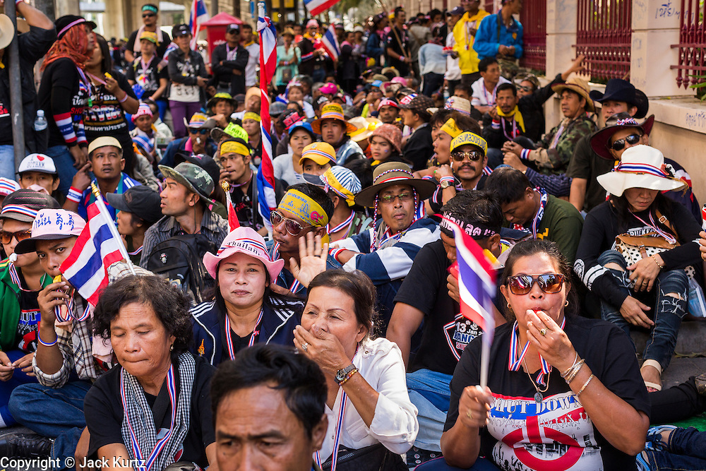 """14 JANUARY 2014 - BANGKOK, THAILAND: Anti-government protestors block the sidewalk in front of Royal Thai Police headquarters. Hundreds of protestors picketed police headquarters because they accuse the police of siding with the government during the protests. Tens of thousands of Thai anti-government protestors continued to block the streets of Bangkok Tuesday to shut down the Thai capitol. The protest, """"Shutdown Bangkok,"""" is expected to last at least a week. Shutdown Bangkok is organized by People's Democratic Reform Committee (PRDC). It's a continuation of protests that started in early November. There have been shootings almost every night at different protests sites around Bangkok, but so far Shutdown Bangkok has been peaceful. The malls in Bangkok are still open but many other businesses are closed and mass transit is swamped with both protestors and people who had to use mass transit because the roads were blocked.     PHOTO BY JACK KURTZ"""