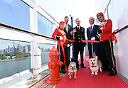 Richard Meadows, center left, President, Cunard, North America, Captain Christopher Wells, center, and David Noyes, center right, CEO, Cunard, joined by Cunard Kennel Masters, cut a ribbon to unveil the remastered kennels on the Queen Mary 2, the only passenger liner to carry pets, Wednesday, July 6, 2016, at Brooklyn Cruise Terminal in New York, its U.S. homeport.  The Queen Mary 2 spent 25 days in dry dock and a refit that cost in the region of $132 million, renovating its staterooms, restaurants and public areas.  (Diane Bondareff/AP Images for Cunard)