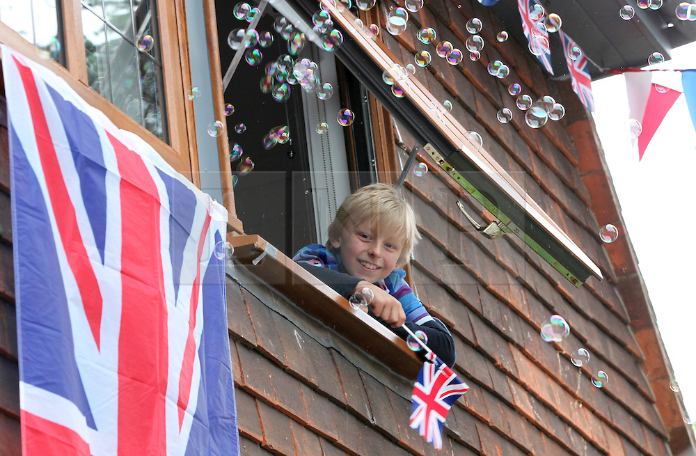 © Licensed to London News Pictures. 04/06/2012. Reading, Berkshire. Finn Nayler waves from the window of his grandparents at a garden party to celebrate The Queen's Diamond Jubilee, Reading. Photo credit : Rebecca Mckevitt/LNP