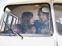 Young couple in camper van smiling at each other view through windscreen
