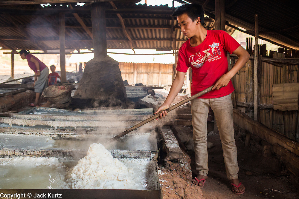 13 MARCH 2013 - BOTEN, LUANG NAMTHA, LAOS:  A worker piles up salt in a workshop in Boten, Laos. Salt in Boten is made by boiling briny water and collecting the salt that is left behind. The salt wells in Boten, Laos, just south of the Chinese border, have brought a measure of fame to the area for centuries. French forces asserted French dominance over the region in 1894 to control the salt trade. Some of the salt works face an uncertain future because of economic development from China. The area is being developed into a huge parking lot to accommodate truck and tourist traffic into and out of China.     PHOTO BY JACK KURTZ