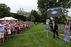 WASHINGTON, DC - JULY 04: White House guests cheer as US President Donald Trump and first lady Melania Trump greet guests during a picnic for military families on July 4, 2018 in Washington, DC. (Photo by Alex Edelman/Getty Images)