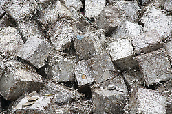 Pile of tin plate bales which have been crushed and baled at a metal recycling centre waiting to be sold on,