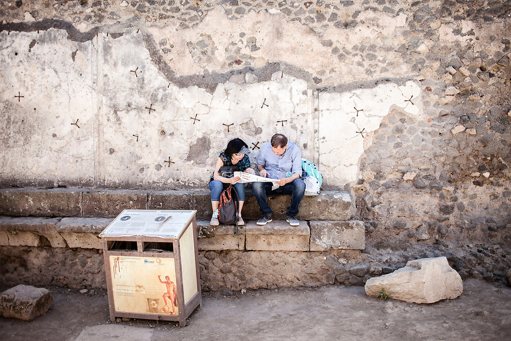 20 May 2017, Pompei, Naples Italy - Two tourists sit on the ruins of the ancient city of Pompeii.