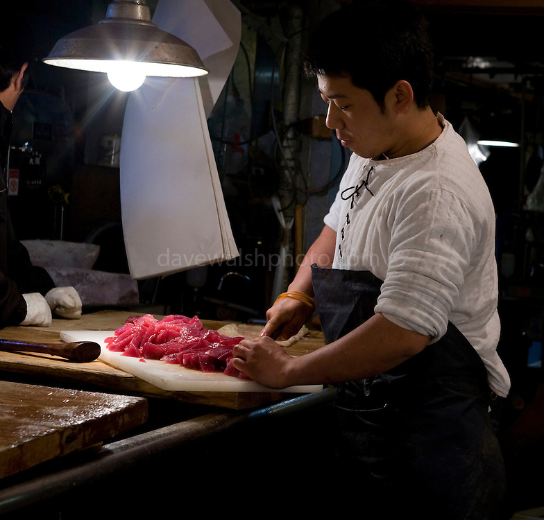Fish market worker cutting up tuna for sushi and sashimi, at Tokyo Metropolitan Central Wholesale Market. Tsukiji Fish Market is the largest fish market in the world.