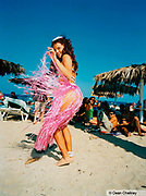 Girl wearing a pink 'grass' skirt on the beach, Ibiza, 2000