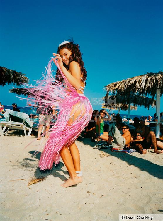 Girl wearing a pink 'grass' skirt on the beach, Ibiza, 2000