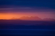 Orange rays of sunrise spotlight the Scottish Highlands including Munros (over 3000 feet elevation) in the Fannichs mountain range, seen across the sea from Digg, near Staffin, on Isle of Skye, Scotland, United Kingdom, Europe.