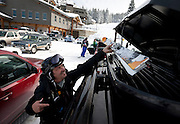 Steve Dellermann tosses a pair of skis into his car top carrier after going out for a few runs at the Brighton Ski Resort, opening on November 13th for the season, Monday, Nov. 12, 2012.