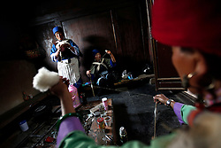 Performers of the Naxi ethnic minority spun cotton in the traditional way in a room backstage prior to their performance in a culture show, the Naxi Impression Show in Lijiang, Yunnan Province, China, 04 April 2012. The Naxi ethnic minority  group is one of the main ethnic minority groups settled in Lijiang, Yunnan province with a unique culture and traditions. The religious Dongba scriptures of the Naxi has been recognised as World Memory Heritage by UNESCO in 2003.